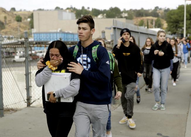 學生在警方護送下撤離校園。(美聯社)