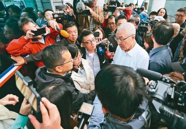 國民黨不分區名單引發爭議,台北市議員羅智強(左下)等青壯派在黨中央前面連夜靜坐,黨主席吳敦義(白衣者)昨早前往溝通。 記者林澔一/攝影
