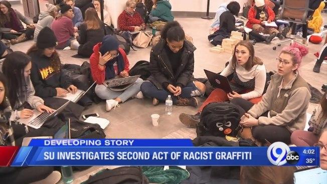 雪城大學校園接連出現貶損亞裔和非裔的種族主義塗鴉,學生靜坐抗議。(取自YouTube)