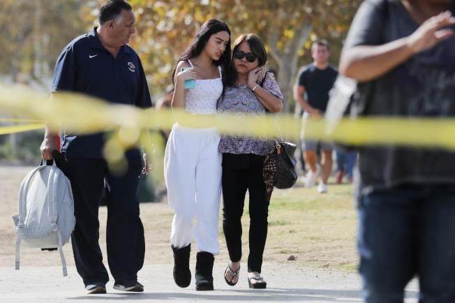 聞訊趕到的家長,安慰驚慌痛哭的學生。(Getty Images)