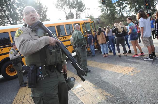 槍擊案發生後,校方把學生撤往安全地點,全副武裝的特警隊員在旁戒備。(Getty Images)