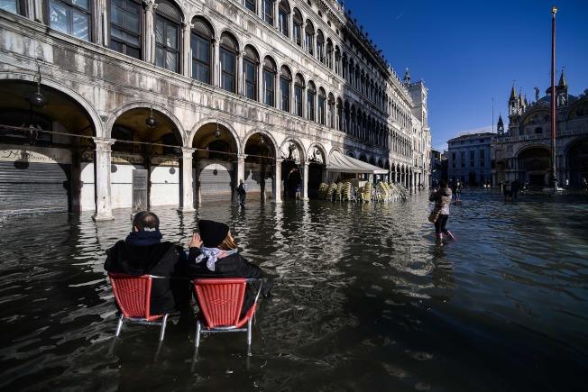 水都威尼斯遭遇半世紀以來最大水患,圖為民眾坐在椅子上,欣賞著名聖馬可廣場的景致。(Getty Images)