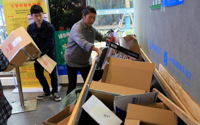 上海交通大學閔行校區內的菜鳥驛站推動「回箱計畫」,一名學生(左)在拆快遞包裝,工作人員(右)則收集整理符合再次使用條件的快遞包裝材料。(新華社)