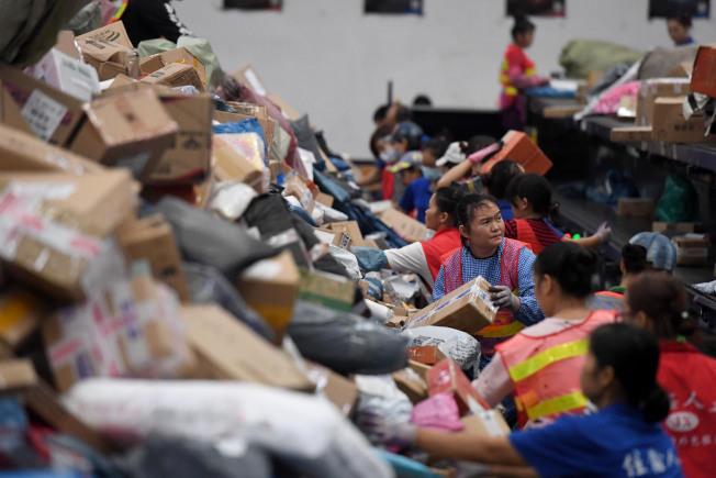 網購狂潮後,由各種紙箱及塑料袋堆起的垃圾山,由誰埋單?(中新社)