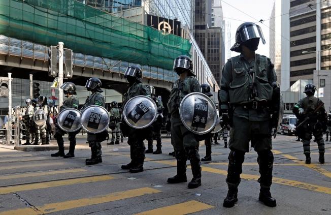 香港防暴警察15日站立於中環一處街道正中央。英國《衛報》13日報導,英國外交部首度有政務官員威脅使用新制裁法,對付侵害人權的港府和港警高層人士。路透