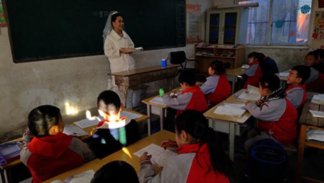 教師劉美迪趁畫完妝等接親的間隙,為不耽誤孩子們上課,穿著婚紗給同學們上了一堂課。(取材自北青網)
