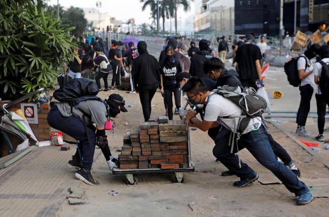 示威抗議者在香港理工大學用推車運輸磚塊與警察對抗。(路透)