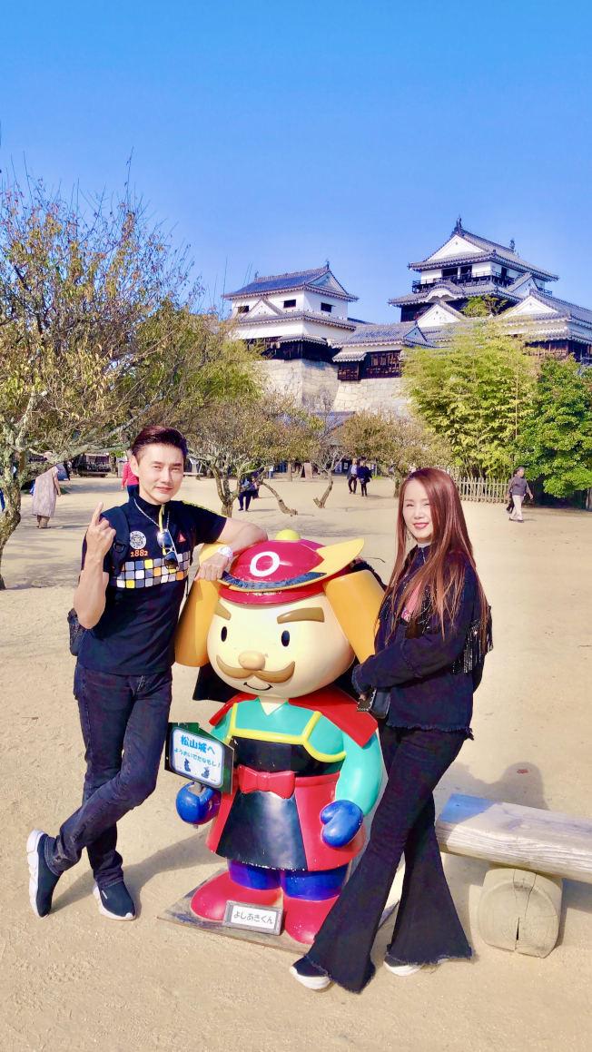 包偉銘與老婆劉依純在松山城日本三大名城之一前與Q版的武士合影留念。(圖:翰森娛樂提供)