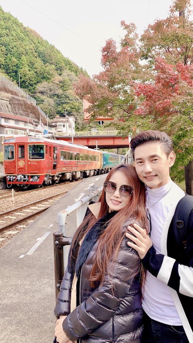 包偉銘(右)與老婆劉依純在千年物語列車的前,與紅楓合影留念。(圖:翰森娛樂提供)