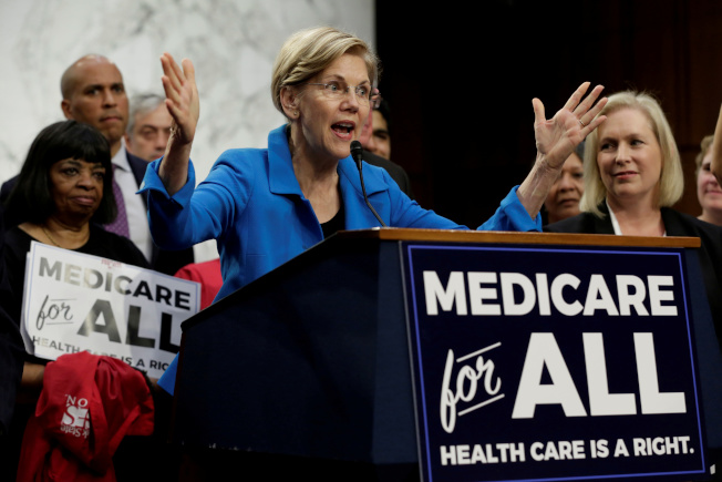 民主黨總統參選人華倫(中)矢言,若當選總統,將在四年內實施全民健保。(路透)