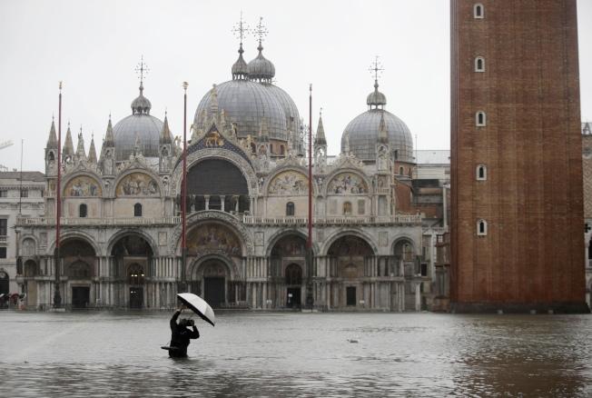 威尼斯景點聖馬爾谷廣場淹水,一名攝影師邊撐傘邊取景。(美聯社)