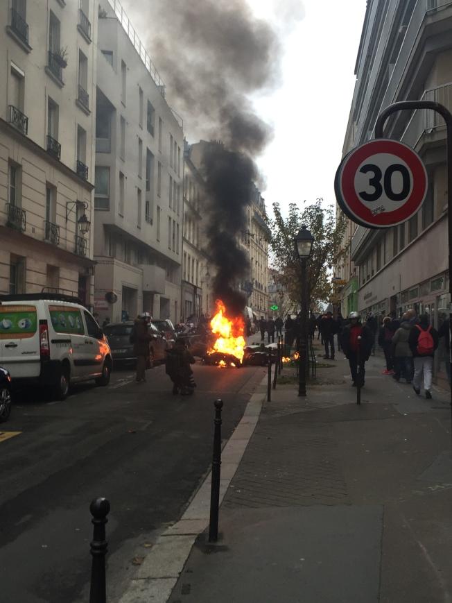 法國黃背心運動一周年爆衝突,部分激進派因不滿警察鎮壓合法申請的集會,開始焚燒汽機車與垃圾桶,現場不斷傳出爆炸聲與濃煙,情況緊張。(中央社)