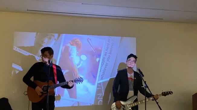 譚仕文(右)在美國華人博物館以彈唱形式講述樂隊經歷。(記者金春香/攝影)