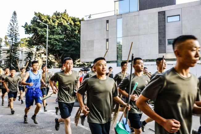 身著便服的駐港解放軍於16日下午自九龍塘駐地跑步上街,清理路障。這是香港示威失控以來,解放軍首次公開出動。(中通社)
