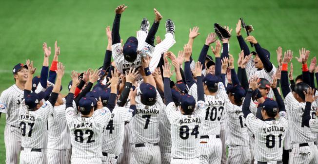 日本隊擊敗南韓奪得12強賽冠軍,賽後球員將總教練稻葉篤紀拋向空中慶賀摘冠。特派記者侯永全/攝影