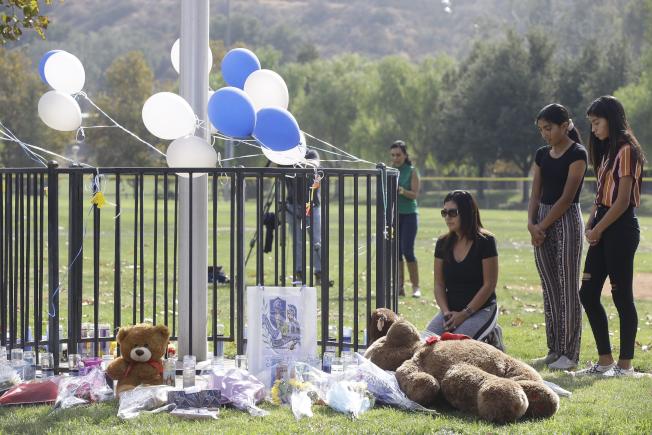 南加州聖塔克拉利塔索格斯高中槍擊案至今,許多民眾不時至公園悼念遇害兩名學生。(美聯社)