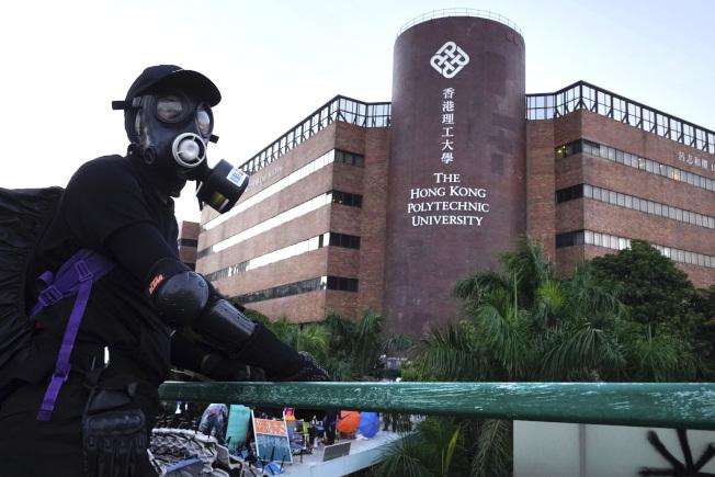 香港反送中示威者17日夜與港警在理工大學外爆發激烈衝突,圖為一名抗議者在理大邊的路橋上。 (美聯社)