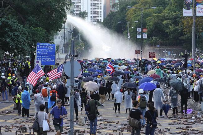 港警17日在香港理工大學外發射藍色水柱,試圖驅散示威者,示威者紛紛撐起傘,阻擋水柱攻擊。(美聯社)