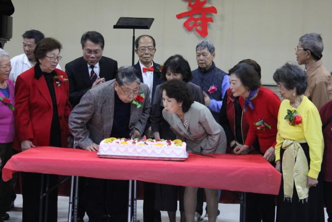 會長趙婉兒(右三)與當日最高齡壽星(左二)一同吹蠟燭慶生。(記者盧淑君/攝影)