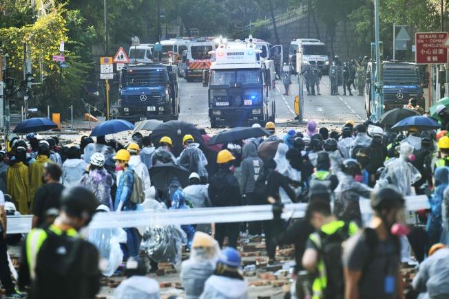 反送中示威者17日在理大外與港警對峙,警方發射藍色水柱,試圖驅散示威者,示威者紛紛撐傘阻擋。(Getty Images)