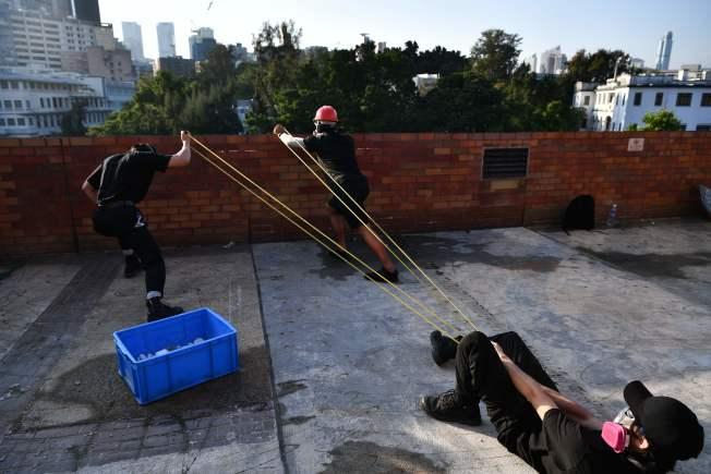 反送中示威者17日在理大內用強大彈弓向港警發射。 (Getty Images)
