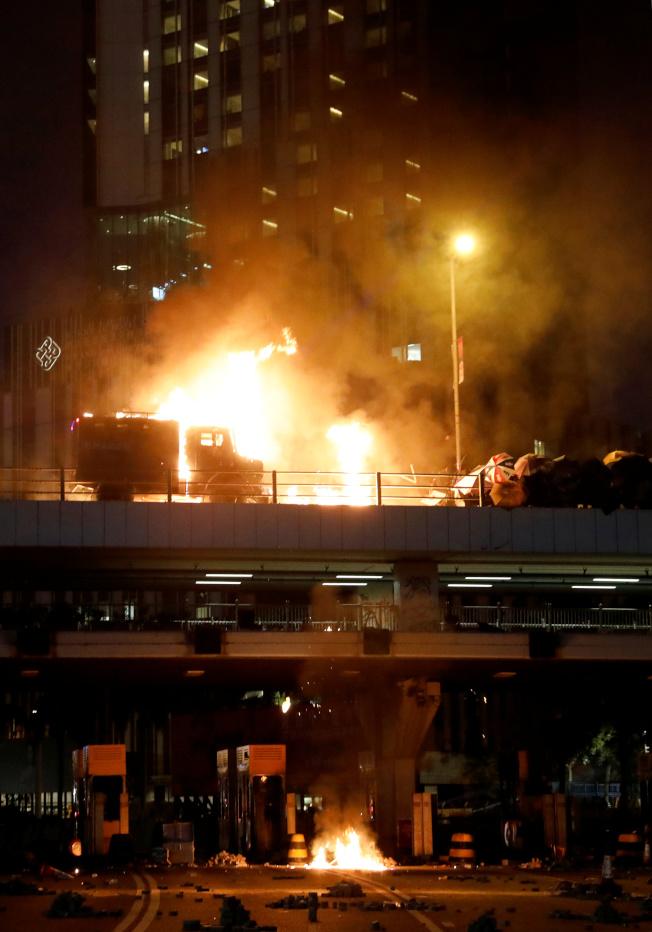 香港反送中示威者17日與警方在理工大學外爆發激烈衝突,示威者向港警投擲汽油彈,造成警察裝甲車著火,燃起熊熊火焰。(路透)