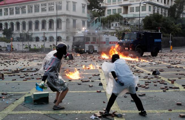 反送中示威者17日在理大外朝港警拋擲汽油彈。(路透)