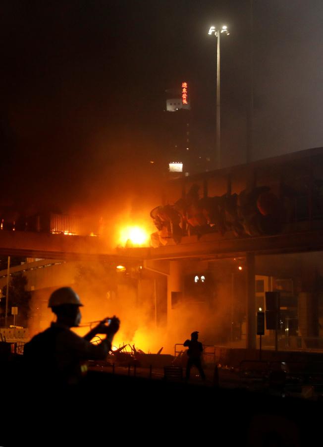 香港反送中示威者17日夜與港警在理工大學外爆發激烈衝突,示威者向港警投擲汽油彈,造成裝甲車著火,燃起熊熊火焰。港警18日清晨攻進理大校園。(路透)