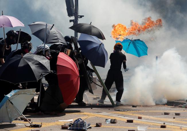 港警17日在理大外發射催淚彈,試圖驅散示威者,示威者紛紛撐傘阻擋,有的傘還著火。(路透)