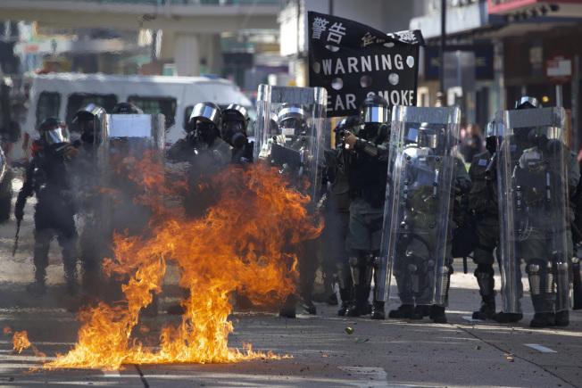 港警17日在理大與反送中示威者對峙,示威者拋擲汽油彈,引發熊熊大火,氣氛緊張。(美聯社)