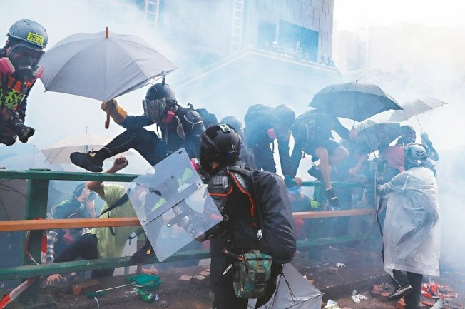 留在香港理工大學的示威者打算逃離,但被警方發射催淚瓦斯逼回校園。警方要求他們舉起雙手投降才能離開校園。 (路透)