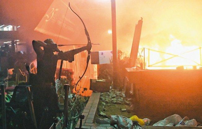 香港理工大學內的激進示威者連日來與警方爆發嚴重衝突,有人持弓箭與警方對抗,圖為18日凌晨有如戰場的理大校園。 中通社