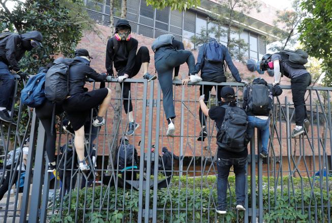 原本在理工大校園內的反送中示威者18日上午試圖翻過鐵網,離開校園,躲避港警追捕。(路透)