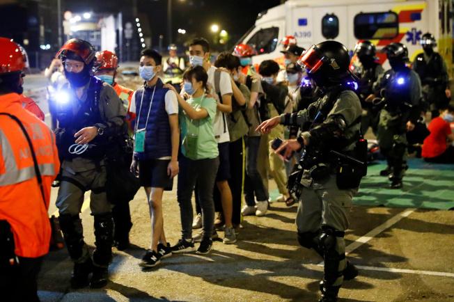 理工大學內的示威者或學生在警方戒護下離開校園。(路透)