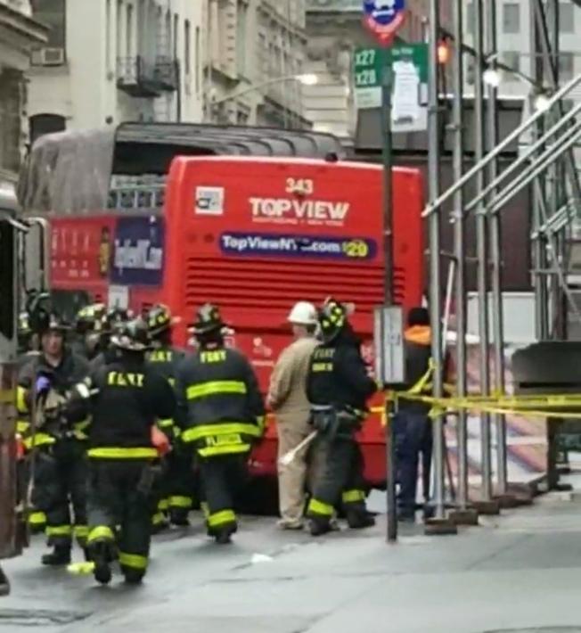 雙層觀光巴士在曼哈頓下城百老匯大道行駛時衝上人行道,險撞倒街邊建築支架。(讀者提供)