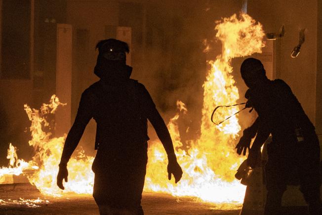 香港特首林鄭月娥表示,有大學校園變成兵工廠,其中一間大學內發現幾千個汽油彈。圖為示威者向警方投擲汽油彈。(美聯社)