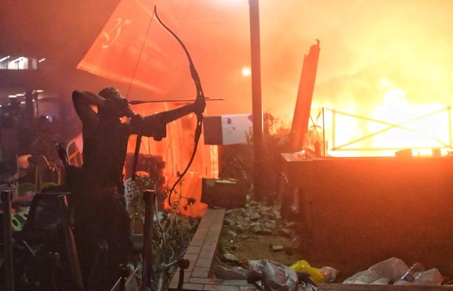 香港理工大學內的激進示威者連日來與警方爆發嚴重衝突,有人持弓箭與警方對抗,圖為18日凌晨有如戰場的理大校園。(中通社)