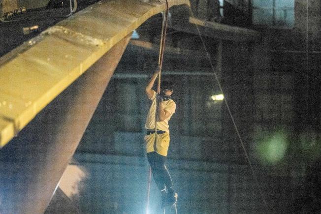一名示威者18日要逃離警方追捕,用繩索把自己自理工大的陸橋降到公路上,非常危險。(Getty Images)