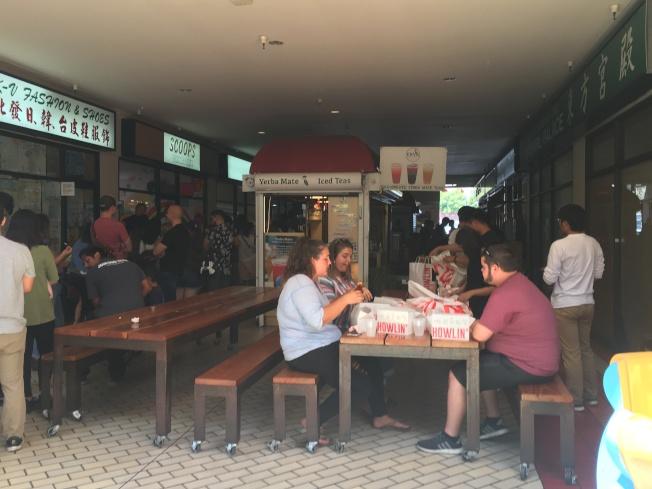 民眾買到炸雞後就馬上坐下來享用。(記者王全秀子/攝影)