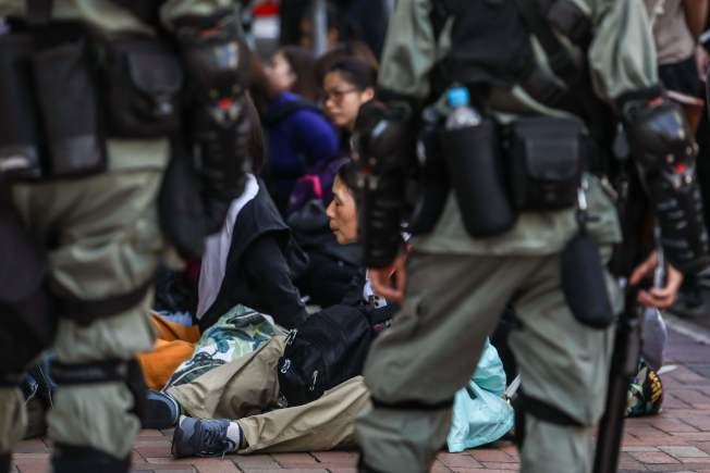 香港警方18日起對理工大校園內的反送中示威者開始清場,被捕的示威者坐在地上等候處理。(Getty Images)