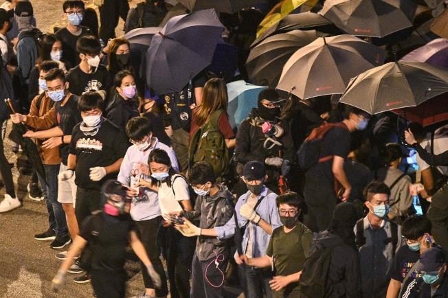 在香港理工大學的示威者18日持續與警方對峙,他們手持成人鏈抵抗警方。(Getty Images)