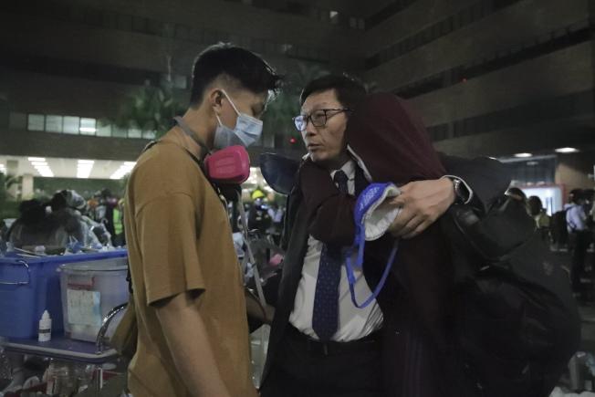 香港警方18日起對理工大校園內的反送中示威者開始清場。一名教師(右)正在勸說一名示威者離開校園。(Getty Images)