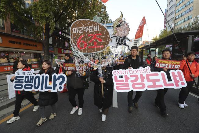 美國與南韓官員18日重啟談判,商討美軍駐紮南韓費用。川普政府要求南韓每年支付50億美元,是目前南韓負擔費用的五倍以上。南韓群眾上街,抗議美國獅子大開口像是「攔路搶劫」。(美聯社)