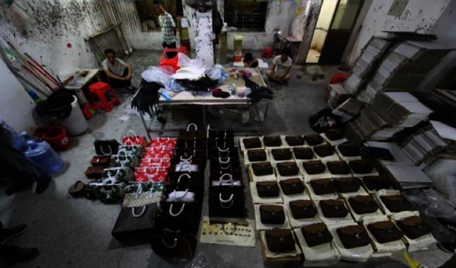 廣東工廠製山寨名牌包,現場堆滿一地。(取材自央廣網)