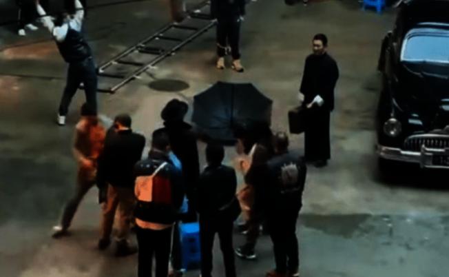 片場視頻中,劉德華拎著箱子站在一旁。(取材自微博)