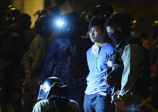 聯合國今天呼籲香港當局「和平解決」警方包圍香港理工大學事件。圖為港警19日逮捕一名從香港理工大學逃出的男子。(美聯社)