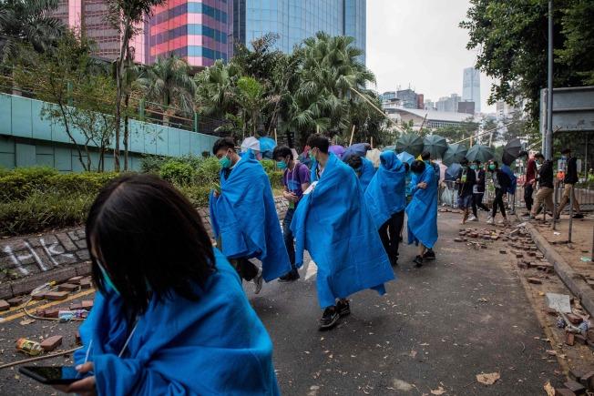 被港警圍困三天的香港理工大學示威者,接受警方條件後自首,19日陸續從校園正門撤出。(Getty Images)