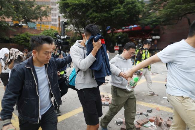 一名向警方投降的示威者,19日用外套遮臉被帶離香港理工大學。(歐新社)