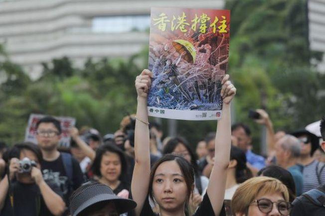 香港遊行人士手持「香港撐住」畫面。(Getty Images)