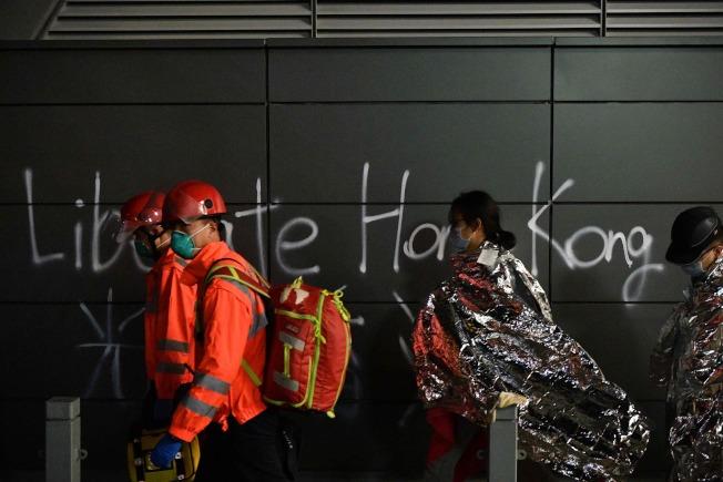 眾議院19日通過「香港人權與民主法案」。圖中,受困香港理工大學的示威者在醫護人員帶領下離開校園。(Getty Images)